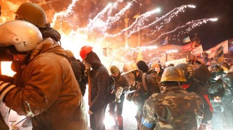 2014年2月18日、キエフの独立広場で、機動隊と衝突する反政府抗議行動参加者達の側で炸裂する花火 ロイター / Yevgeny Volokin