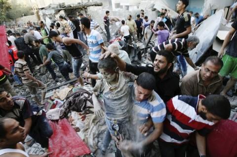 日曜日、南部ガザ、ラファの住宅アパートを狙ったイスラエル空爆の生存者を救出するパレスチナ人 AP/Eyad Baba