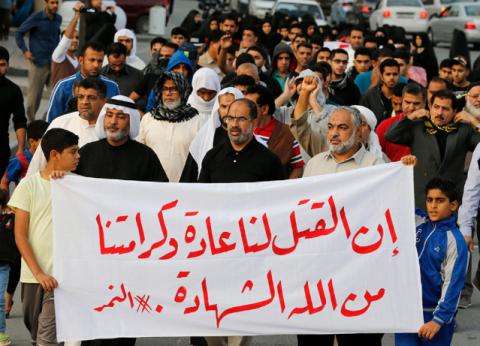 """2016年1月2日 バーレーン、マナマ西部のサナビス村で、サウジアラビア当局による、サウジアラビアのシーア派宗教指導者ニムル・アル-ニムルの処刑に反対する抗議行動で、 """"死は我々にとって当然のことで、神があたえたもうた尊厳は殉教だ"""" という垂れ幕を掲げる参加者、Hamad I Mohammed / Reuters"""