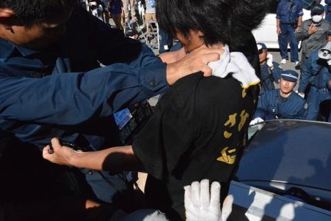 街宣車の屋根にのぼって来た機動隊員から首を絞められる男性。=22日午前8時50分頃、東村高江 撮影:筆者=