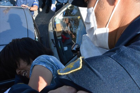 街宣車の上から落とされそうになり悲鳴をあげる女性。反対派住民のマイカーが下に見える。=22日午前8時50分頃、東村高江 撮影:筆者=