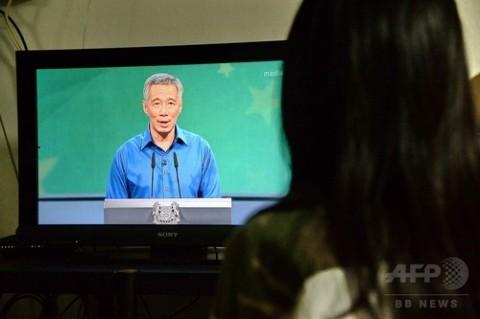 体調不良を起こした後、演説を再開したシンガポールのリー・シェンロン首相のテレビ生中継を見守る視聴者(2016年8月21日撮影)。(c)AFP/ROSLAN RAHMAN