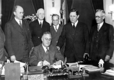 【中央に座っているのが、金準備法に署名するルーズベルト大統領】