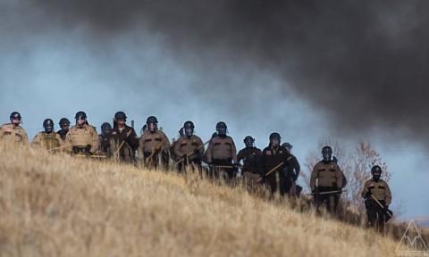 (画像 民間企業の利益を守るために武装化して抗議活動に対うする警察)  http://www.yesmagazine.org/